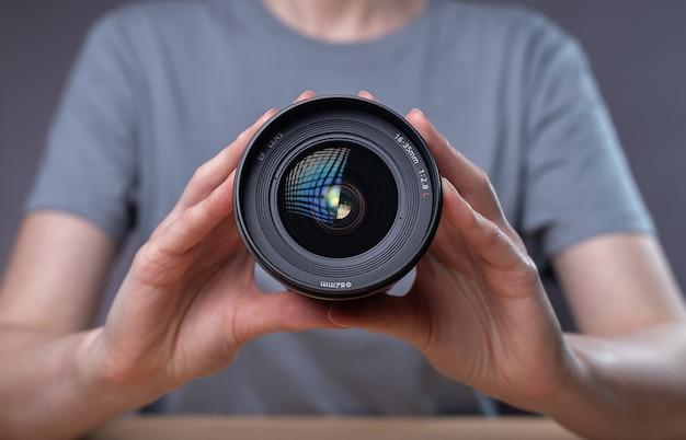 Modern digital camera lens in hands of female photographer.