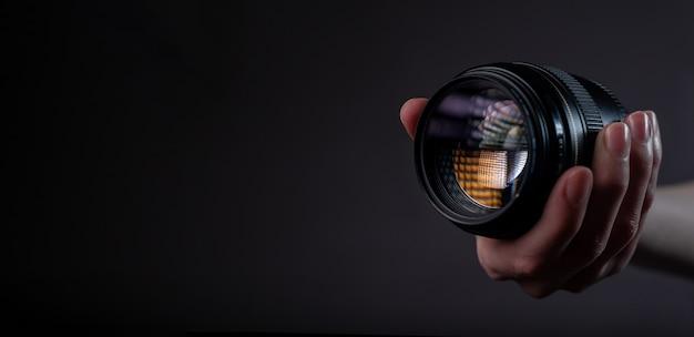 Современный объектив цифровой камеры 85 мм в руке на темно-черном сером фоне с местом для текста.