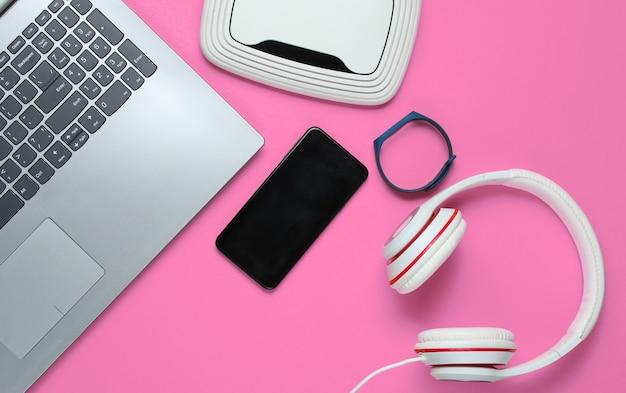 現代のデジタルガジェットとアクセサリー。ラップトップ、スマートフォン、スマートブレスレット、ヘッドフォン、ピンクの背景のwi-fiルーター。上面図。
