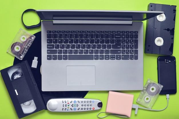 Современные цифровые гаджеты, носители данных и устаревшие аналоговые мультимедийные устройства на зеленой поверхности