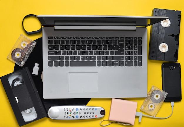 黄色の紙の背景にある現代のデジタルガジェット、ストレージメディア、古くて時代遅れのアナログメディアデバイス。上面図。平干し。