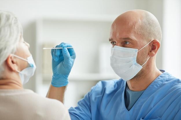 Современный врач в маске сидит перед пожилым пациентом, берущим мазок из носа на коронавирус
