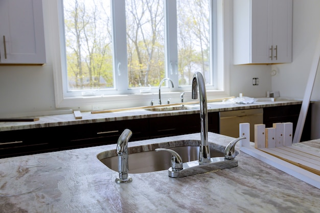 Современные бытовые шкафы с новой бытовой техникой и раковиной на кухне