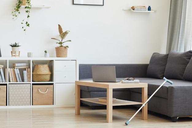 Современная домашняя гостиная с ноутбуком на столе и большим диваном