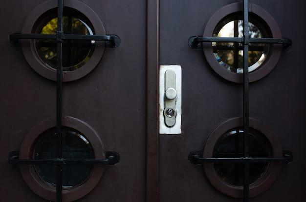 Современная дверь с металлической ручкой и окошечком. снимок крупным планом