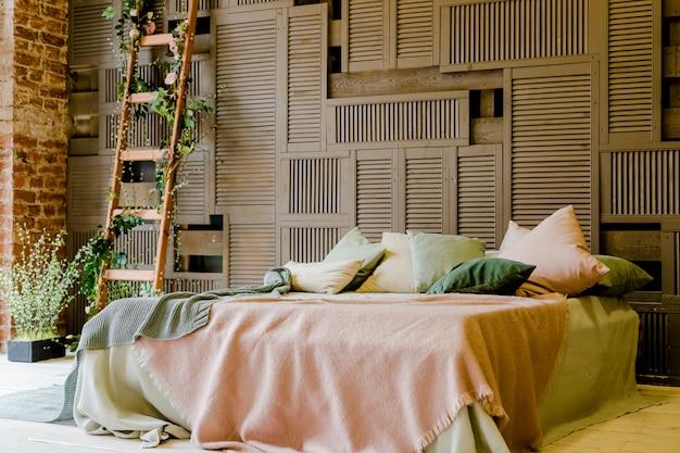 木製の壁に立っているモダンなダブルベッド。緑とピンクの居心地の良い枕とインテリア。居心地の良いキングサイズのベッドを備えたスタイリッシュなベッドルーム。ロフトスタイル
