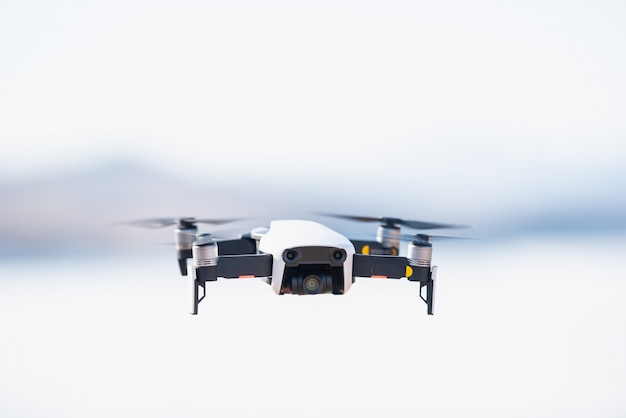 Modern drone with camera flying on blue sky background.
