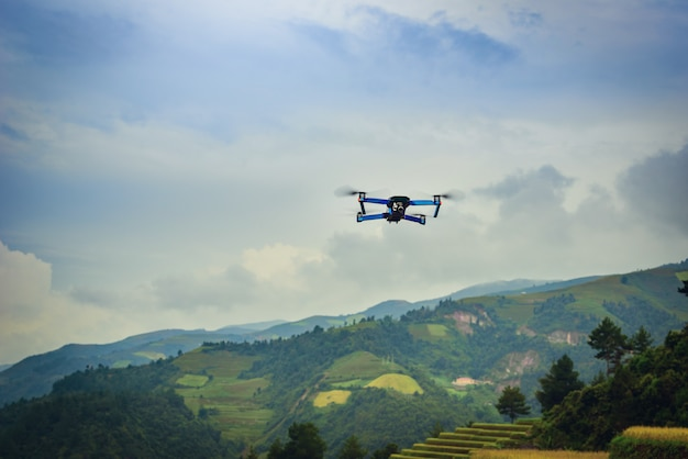 Modern drone with camera flying on rice fields terraced at sunset in vietnam.