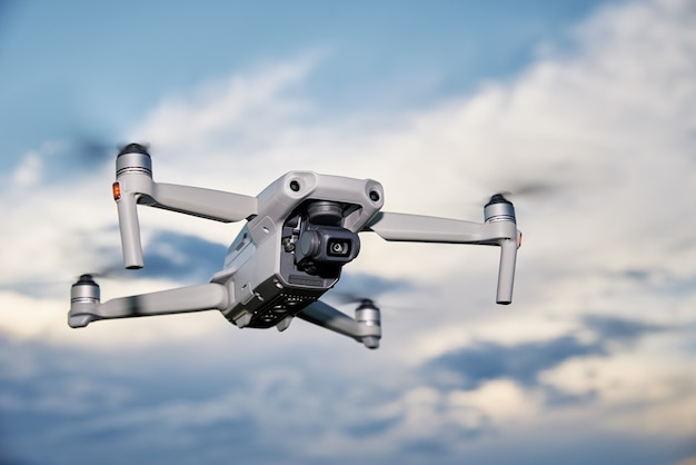 Modern drone with camera in the sky. flying quadcopter