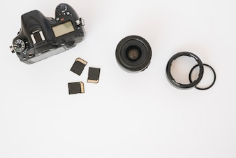 Modern dslr camera; memory cards and camera lens with extension rings on white backdrop