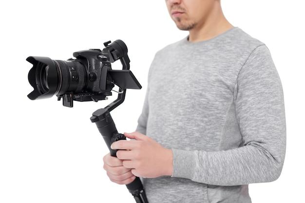 흰색 배경에 격리된 비디오그래퍼 손에 있는 3축 짐벌 안정기에 있는 최신 dslr 카메라