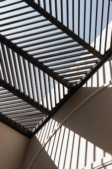 ベージュの壁と壁にレールの日光の影があるモダンなイーストスタイルの建物。