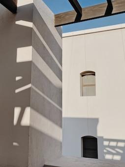 Современное здание в восточном стиле с бежевыми стенами, окнами и рельсами в тени солнечного света