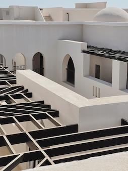 ベージュの壁、窓、レールの日光の影があるモダンなイーストスタイルの建物