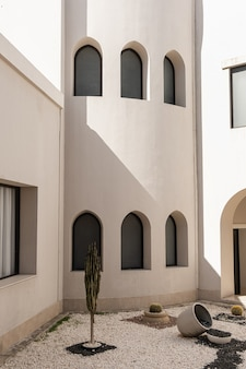 Modern east style building with windows and sunlight shadows on beige walls