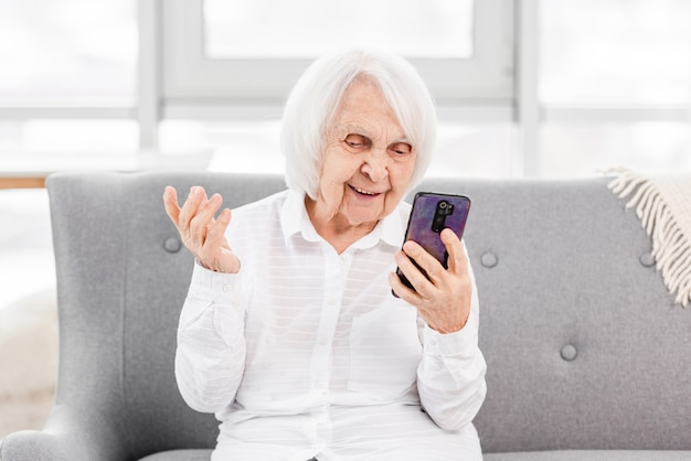 Modern ederly woman sitting at the sofa at home and talking with friends by video using smartphone