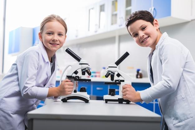Современное образование. позитивные умные милые дети улыбаются и смотрят на вас во время урока биологии