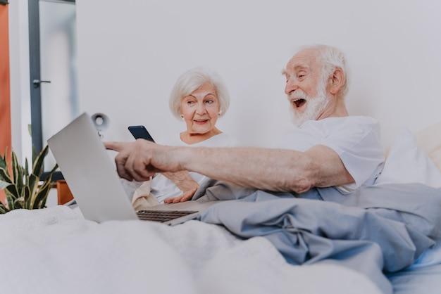 Modern elderly couple surfing the internet on laptop computer