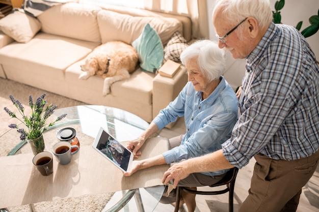 Modern elderly couple using digital tablet