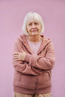 快適なパーカーの交差する腕を身に着けている短い銀の髪を持つ現代の年配の女性