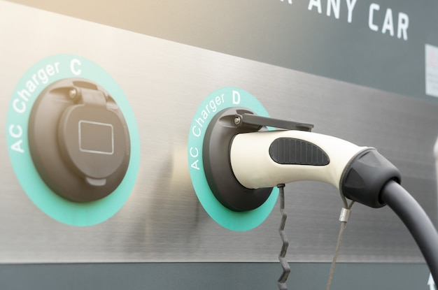 Modern electric car charger plug in ev charging station, no pollution green fuel power or hybrid vehicle technology