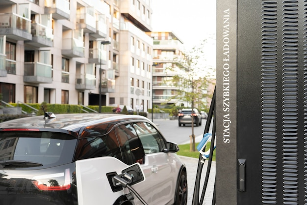 A modern electric car connected by a cable to a power supply unit charges the batteries at a city fast charging station