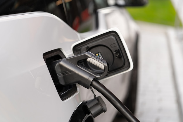 A modern electric car connected to a power supply unit charges the batteries at a fast charging station