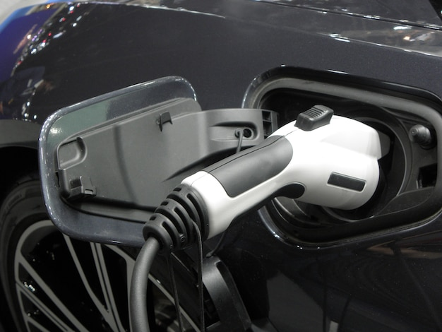 Современный электромобиль белого цвета на зарядке от сети. экологичность, транспорт будущего