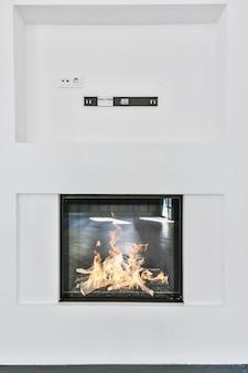 リビングルームの白い壁に設置されたガラススクリーン付きのモダンな電気暖炉