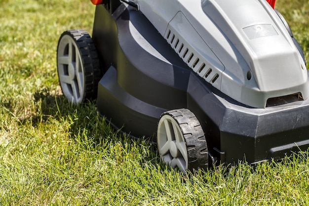 Modern electric lawn mower on freshly trimmed sward with green grass