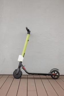 街の灰色の壁の近くにあるモダンな電動スクーター。エコロジー輸送の概念。