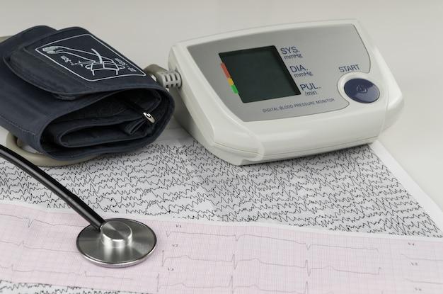 心電図チャート上の最新の心電図と聴診器。家庭用血圧計