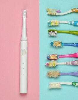Современная электрическая зубная щетка и старые использованные зубные щетки на розово-голубом пастельном фоне. вид сверху