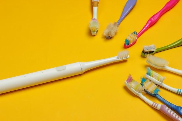 Современная электрическая зубная щетка и старые использованные зубные щетки на желтом фоне. вид сверху