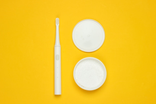 Современная электрическая зубная щетка и зубной порошок на желтом фоне. концепция стоматологической помощи. вид сверху. минимализм