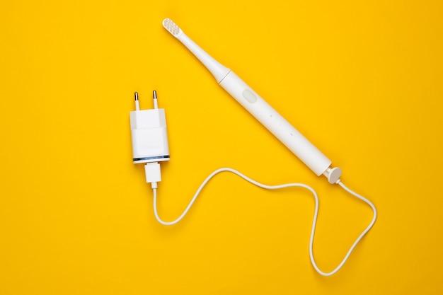 Современная электрическая зубная щетка с зарядным устройством на желтом фоне. вид сверху
