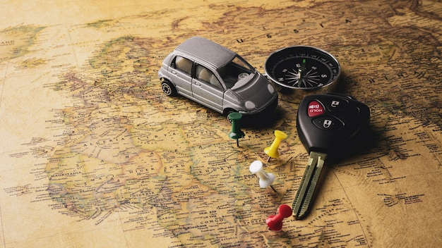 Modern electronic car keys and compass on vintage map. - travel and adventure concept backdrop.