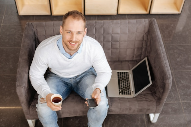Modern electronic device. delighted positive nice man sitting on the sofa and holding his smartphone while looking at you