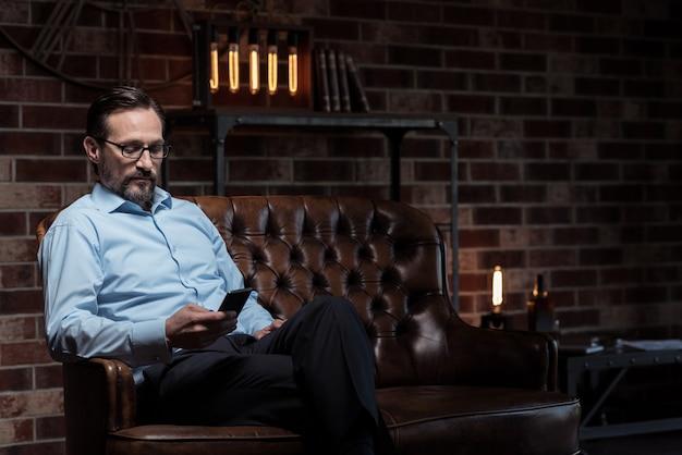 現代の電子機器。ソファに座って彼の足を組んで携帯電話を見ているハンサムな勤勉な大人の男