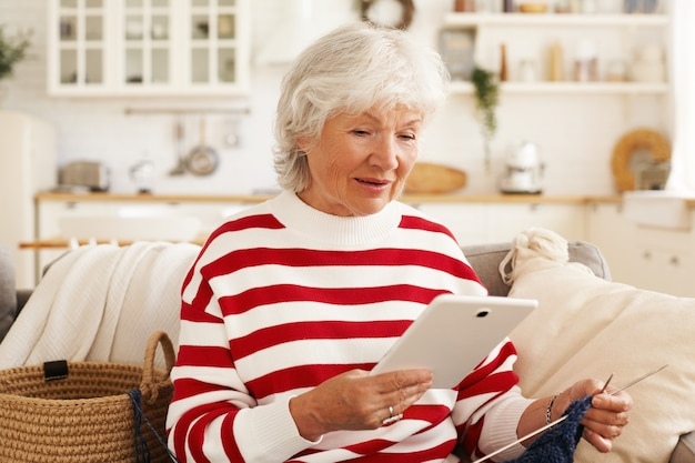 現代の電子ガジェット、デバイス、接続および通信の概念。魅力的な年配の女性が自宅で編み物をし、毛糸でソファに座って、デジタルタブレットを介してオンラインでビデオチュートリアルを見る