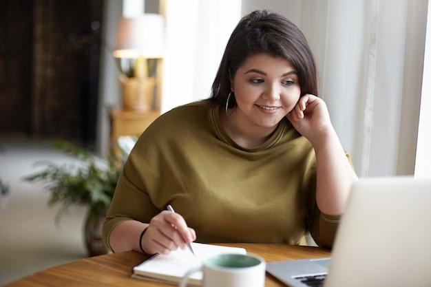 현대 전자 기기, 직업 및 직업 개념. 원격 작업을 위해 랩톱 컴퓨터를 사용하여 초과 체중을 가진 귀여운 우아한 젊은 갈색 머리 여성, 화면을보고, 펜을 들고, 적어
