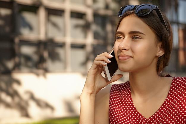 現代の電子ガジェット、人、コミュニケーションの概念。友人との素敵な会話をしながら、携帯電話で話している点線の赤いドレスを着た美しい日焼けしたヨーロッパの女性のクローズアップショット