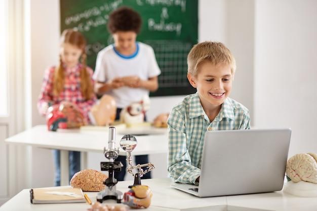 현대 전자. 공부를 위해 노트북을 사용하는 동안 화면을보고 행복 어린 소년