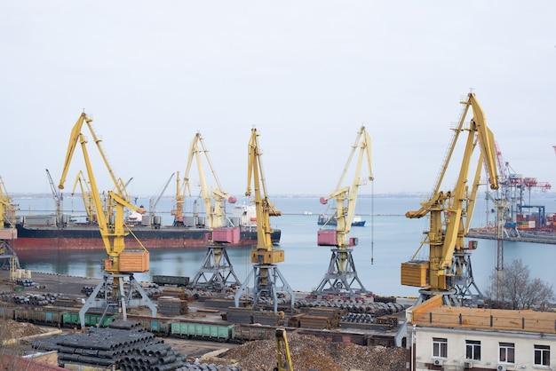 海岸クレーンのジブとばら積み貨物の山が積み込まれ、配達される準備ができている、近代的な高架道路と港湾の産業景観。ロジスティック輸送。