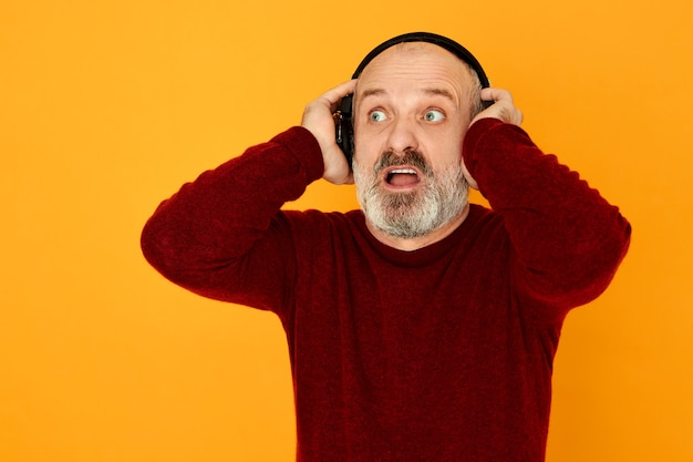 Uomo anziano emotivo moderno con barba grigia che guarda lontano tenendo la bocca aperta ascoltando brutte notizie spaventose alla radio, scioccato e terrorizzato.