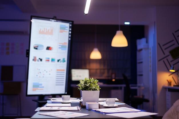 現代の空のビジネス企業のオフィスの会議室は、深夜にビジネスマンのために用意されています。経済グラフと会議テーブル立っている会社の財務文書の背景に