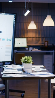 現代の空のビジネス企業のオフィスの会議室は、深夜にビジネスマンのために用意されています。経済グラフ付きの会議テーブルスタンディング会社の財務書類の背景に