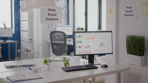 プラスチック製のセパレーターと壁に社会的な距離のポスターを保持するモダンな空のオフィスのインテリア。誰もいない空の企業スペースビジネスインテリア