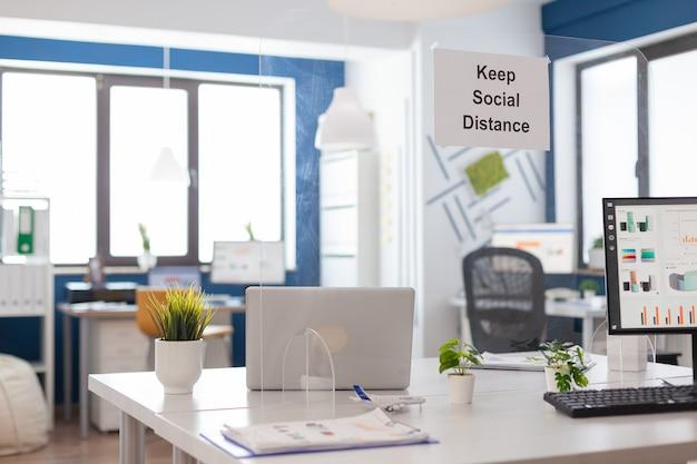 플라스틱 분리기가 있는 현대적인 빈 사무실 내부와 벽에 사회적 거리 포스터를 붙입니다. 아무도 없는 빈 기업 공간 비즈니스 인테리어.