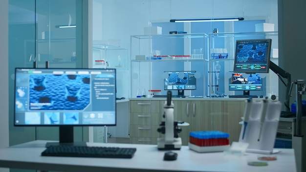 Современная пустая научно-исследовательская лаборатория прикладных наук с технологическими микроскопами, стеклянными пробирками, микропипетками, настольными компьютерами и дисплеями. компьютеры выполняют сложные расчеты днк.